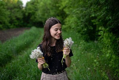 Smiling teenage girl holding dandelions in a field - p1427m2123594 by vyacheslav chistyakov