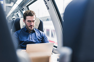 Businessman working in train using laptop - p300m1562384 by Uwe Umstätter