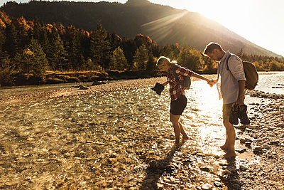 Austria, Alps, couple on a hiking trip wading in a brook - p300m2081333 by Uwe Umstätter