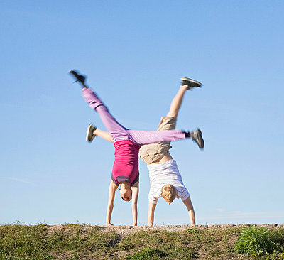 Mid adult couple doing cartwheel in a park - p3741488 by Olli-Pekka Orpo