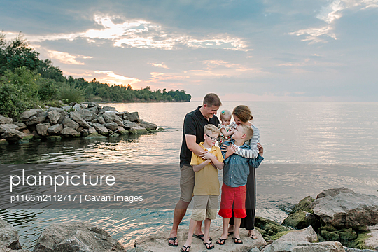 Happy family standing on rocks at beach against cloudy sky during sunset - p1166m2112717 by Cavan Images
