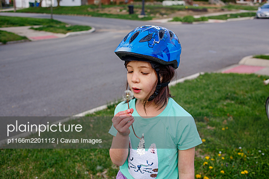 A little girl in a bike helmet blows the seeds of a dandelion flower - p1166m2201112 by Cavan Images