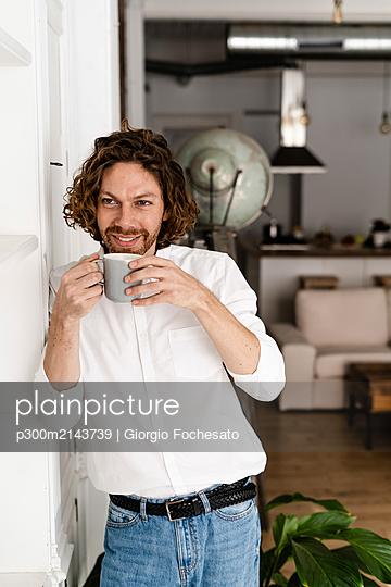 Smiling man having a coffee break at home - p300m2143739 by Giorgio Fochesato