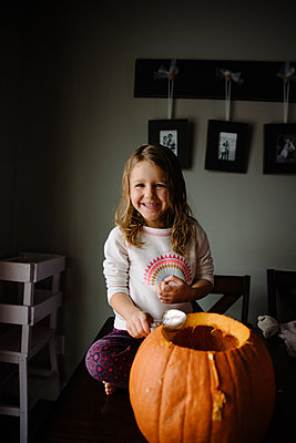 Girl carving pumpkin and scooping out seeds on her kitchen table home - p1166m2269347 by Cavan Images