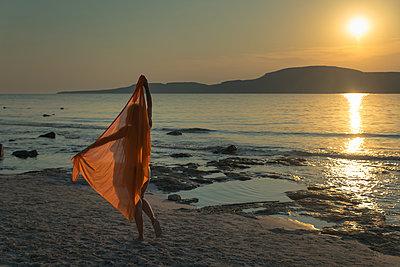 Die Silhouette einer Frau in ein oranges Tuch gehüllt während eines Sonnenuntergangs am Meer  - p1400m1475085 von Bastian Fischer