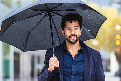 Smiling entrepreneur holding umbrella in city during rainy season - p300m2227106 by NOVELLIMAGE