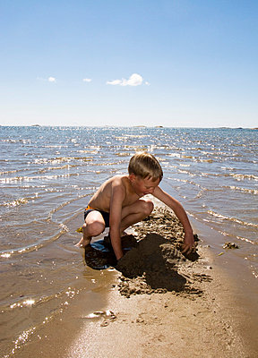 Boy on the beach - p3226273 by plainpicture