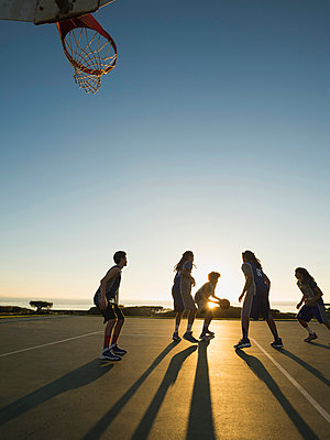 Back lit basketball teams playing on court - p555m1415527 by Erik Isakson