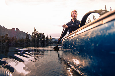 Young man canoeing on Echo Lake, High Sierras, California, USA - p924m2008821 by Alex Eggermont
