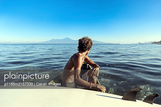 Side view of anonymous man with surfboard sitting in rowboat - p1166m2157339 by Cavan Images