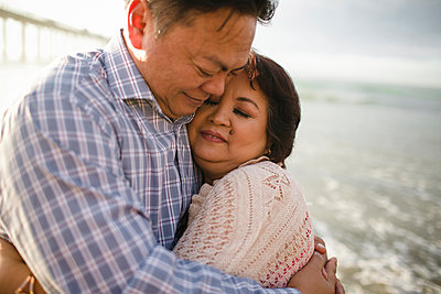 Close-up of couple embracing while standing at beach - p1166m1404116 by Cavan Images