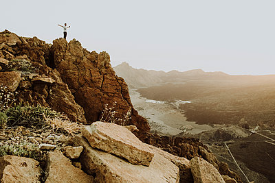 Pulled back view of man standing on mountain top at Ca̱adas del Teide - p1166m2129943 by Cavan Images