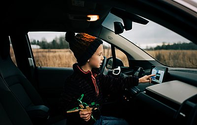 young boy sat in the drivers seat of an electric car using sat nav - p1166m2157401 by Cavan Images