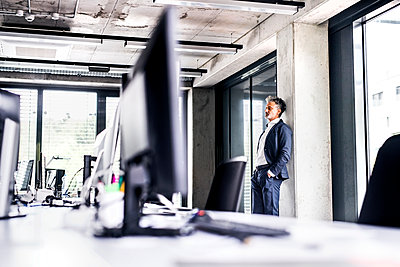 Mature businessman standing in office thinking - p300m1535520 by HalfPoint