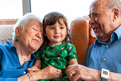 Grandparents spending time with the granddaughter in living room - p300m2139920 by Gemma Ferrando