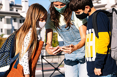Mother and kids wearing protective face mask using smart phone standing in public park on sunny day - p300m2225883 by Jose Luis CARRASCOSA