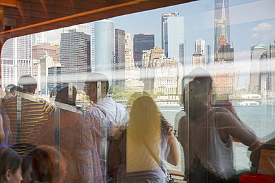 Reflection of people on Staten Island Ferry looking at buildings, New York City, New York, USA - p301m1534990 by Marc Volk