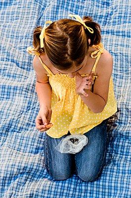 Caucasian girl eating snack on picnic blanket - p555m1409114 by Shestock