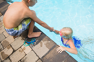 Caucasian boy helping sister out of swimming pool - p555m1421672 by JGI/Jamie Grill