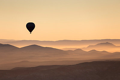 Single hot air balloon over a misty dawn sky, Cappadocia, Anatolia, Turkey, Asia Minor, Eurasia - p871m1013114 by David Clapp