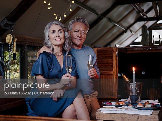 Portrait of senior couple having a candlelight dinner on a boat in boathouse - p300m2156232 by Gustafsson