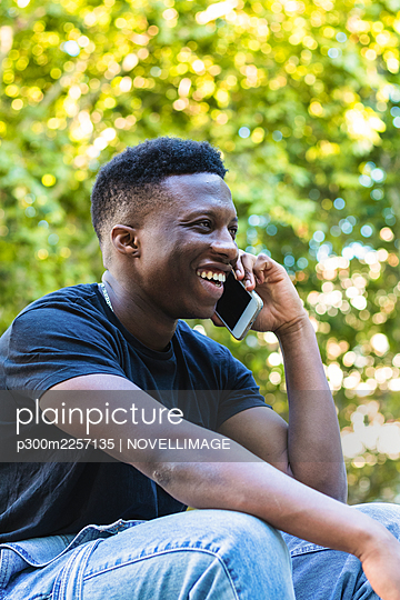Smiling young man talking on smart phone while sitting in park - p300m2257135 by NOVELLIMAGE