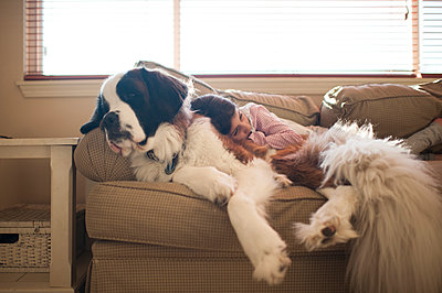Girl relaxing with Saint Bernard on sofa at home - p1166m1230448 by Cavan Images