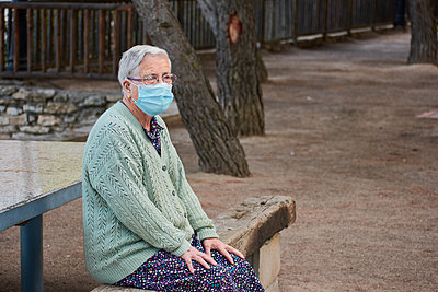 Grandmother is sitting on a bench with her mask on - p1166m2218075 by Cavan Images