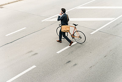 Businessman with bicycle on cell phone walking on the street - p300m2004785 by Uwe Umstätter