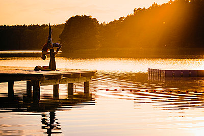 Women practicing acro yoga on lakeside dock at sunset - p301m2075547 by Sven Hagolani