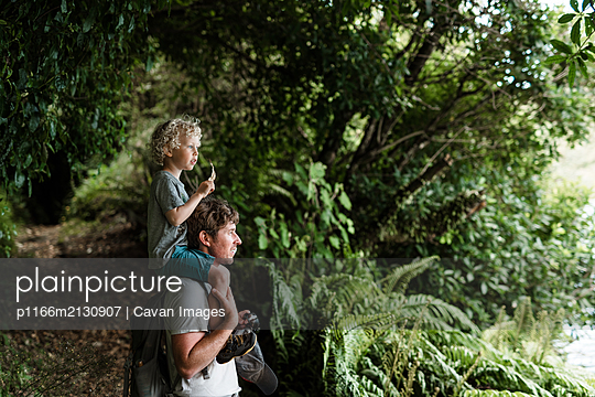 Young child sitting on father's shoulders in a forest - p1166m2130907 by Cavan Images