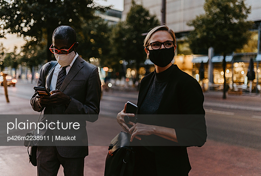 Male and female colleagues standing with smart phone on footpath during pandemic - p426m2238911 by Maskot