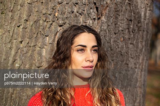 Junge Frau lehnt an einem Baumstamm - p975m2222114 von Hayden Verry