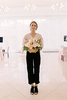 Portrait of confident woman holding bouquet while standing on tiled floor in ceremony - p1166m2034123 by Cavan Images