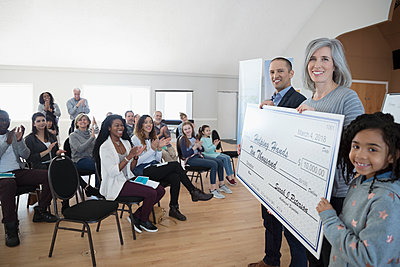 Portrait smiling community clapping, presenting large donation check - p1192m1560334 by Hero Images