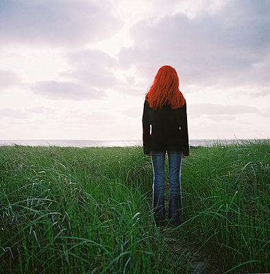 Young woman stares at the sea - p1231m2043346 by Iris Loonen