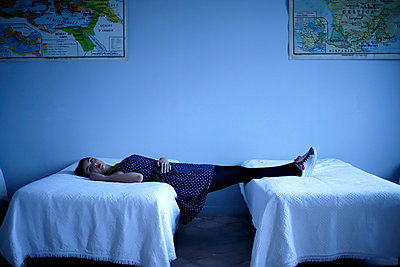 Young woman lying between two beds - p1521m2128962 by Charlotte Zobel