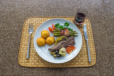 Lamb fillet with croquettes, green beans bacon-wrapped, artichoke, tomato and chili pepper, red wine glass - p300m1130152f von Patrice von Collani