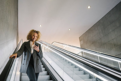 Smiling woman using cell phone on escalator - p300m2143419 by Hernandez and Sorokina