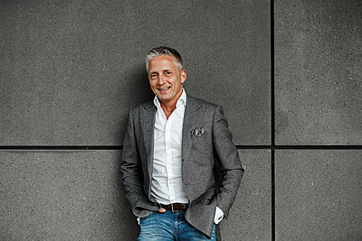 Handsome male entrepreneur with hands in pockets standing against gray wall - p300m2276507 by Sandro Jödicke