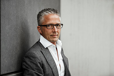 Businessman with eyeglasses in front of gray wall - p300m2277429 by Sandro Jödicke