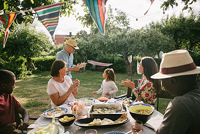 Family applauding at senior man and girl dancing during garden party - p426m2036620 by Maskot