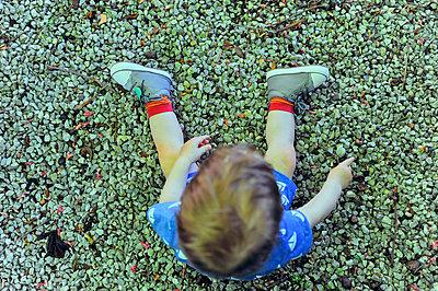 Kind sitzt auf Kieselsteinen - p900m1475074 von Michael Moser