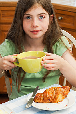 Girl drinking hot chocolate with croissant - p9243131f by Image Source