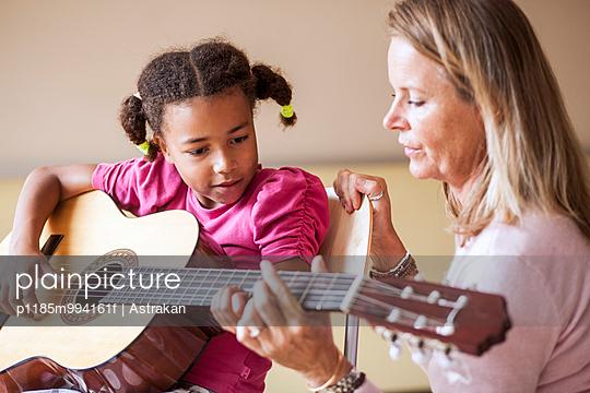 Mature female teacher teaching girl to play guitar in class