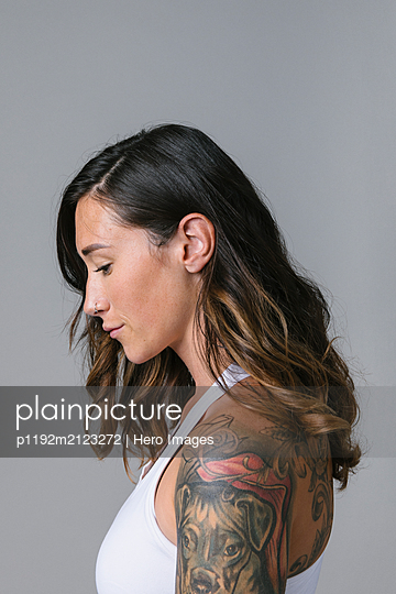 Profile portrait serene young woman with shoulder tattoo and nose ring - p1192m2123272 by Hero Images
