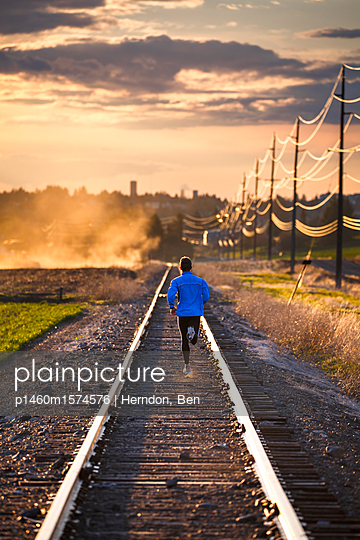 Man on an evening run along abandoned railroad tracks near Pullman, Washington at sunset. The dust cloud is from nearby farming activity.                           - p1460m1574576 by Herndon, Ben