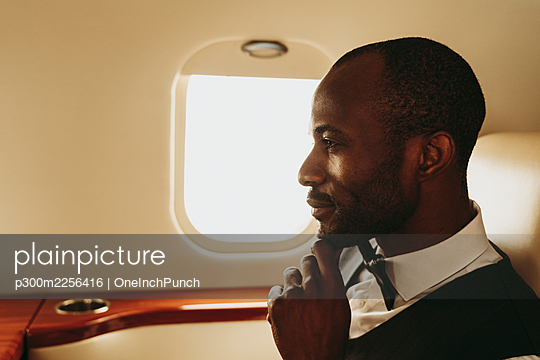 Thoughtful businessman with hand on chin in private jet - p300m2256416 by OneInchPunch