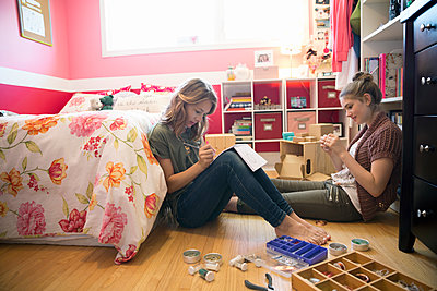 Girls making jewelry in bedroom - p1192m1158030 by Hero Images