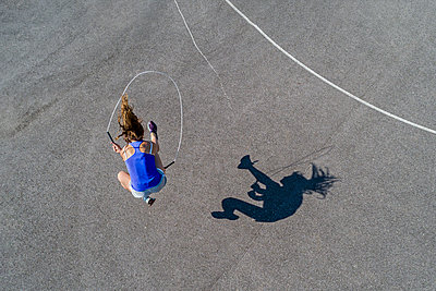 Aerial view of young woman skipping rope, shadow - p300m2004736 von Stefan Schurr